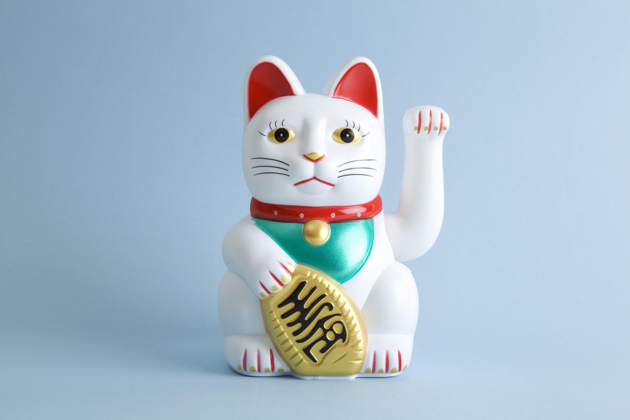 a Maneki-neko plastic cat, Symbolizing luck and wealth, on a pop and colorful background. Minimal color still life photography